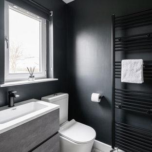 グラスゴーのコンテンポラリースタイルのおしゃれな浴室 (フラットパネル扉のキャビネット、グレーのキャビネット、黒い壁、一体型シンク、グレーの床、白い洗面カウンター、洗面台1つ、フローティング洗面台) の写真