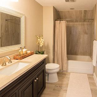 Esempio di una stanza da bagno con doccia american style di medie dimensioni con ante con bugna sagomata, ante nere, vasca ad alcova, vasca/doccia, WC a due pezzi, pareti beige, pavimento in gres porcellanato, lavabo sottopiano, top in granito, pavimento beige e doccia con tenda
