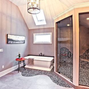 シカゴの大きいラスティックスタイルのおしゃれなマスターバスルーム (置き型浴槽、コーナー設置型シャワー、シェーカースタイル扉のキャビネット、中間色木目調キャビネット、分離型トイレ、黒いタイル、石タイル、ベージュの壁、玉石タイル、オーバーカウンターシンク、珪岩の洗面台、黒い床、開き戸のシャワー) の写真