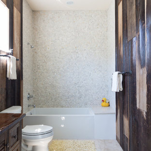 Immagine di una piccola stanza da bagno con doccia stile rurale con ante in stile shaker, ante in legno bruno, vasca/doccia, piastrelle bianche, piastrelle di ciottoli, top in legno, WC a due pezzi, pareti marroni, pavimento con piastrelle in ceramica, lavabo sottopiano e top marrone