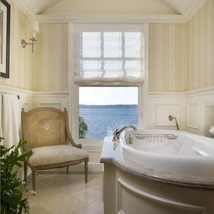 Ispirazione per una stanza da bagno tradizionale con ante con riquadro incassato, ante beige, vasca da incasso e piastrelle beige