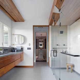 Ejemplo de cuarto de baño principal, contemporáneo, grande, con lavabo bajoencimera, armarios con paneles lisos, puertas de armario de madera oscura, ducha a ras de suelo, paredes blancas, suelo de baldosas de porcelana, encimera de cuarzo compacto, suelo gris y ducha con puerta con bisagras