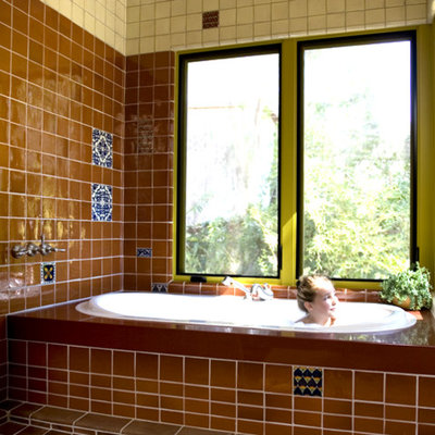 Mid-sized southwest brown tile, white tile and ceramic tile terra-cotta tile and red floor bathroom photo in Los Angeles with an undermount tub and quartz countertops
