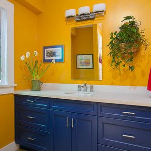 Ejemplo de cuarto de baño clásico, de tamaño medio, con lavabo bajoencimera, armarios con paneles empotrados, puertas de armario azules, ducha abierta, sanitario de dos piezas y paredes amarillas
