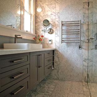 バンクーバーの中サイズのトランジショナルスタイルのおしゃれなマスターバスルーム (ベッセル式洗面器、シェーカースタイル扉のキャビネット、グレーのキャビネット、クオーツストーンの洗面台、分離型トイレ、グレーのタイル、石タイル、グレーの壁、大理石の床、置き型浴槽、段差なし) の写真