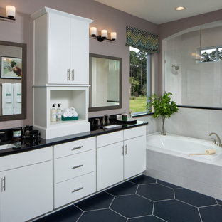 Example of a transitional master blue floor drop-in bathtub design in Jacksonville with flat-panel cabinets, white cabinets, purple walls, an undermount sink and black countertops