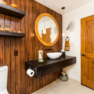 Bathroom - mid-sized southwestern 3/4 porcelain floor bathroom idea in Albuquerque with a vessel sink, dark wood cabinets, wood countertops, beige walls and a two-piece toilet