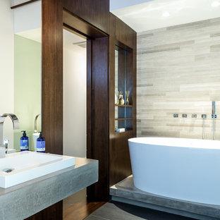 Неиссякаемый источник вдохновения для домашнего уюта: ванная комната в стиле лофт с накладной раковиной, темными деревянными фасадами, отдельно стоящей ванной, душем над ванной и серой плиткой