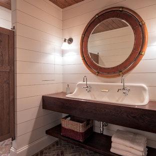 Klassisk inredning av ett mellanstort badrum med dusch, med öppna hyllor, skåp i mörkt trä, vita väggar, tegelgolv, ett avlångt handfat, träbänkskiva och rött golv