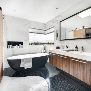 Bathroom - mid-sized modern master white tile and stone slab marble floor and white floor bathroom idea in Orange County with flat-panel cabinets, medium tone wood cabinets, a two-piece toilet, white walls, an integrated sink, quartz countertops, a hinged shower door and white countertops