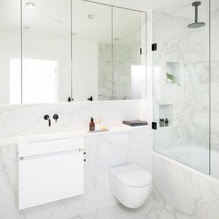 Mittelgroßes Modernes Badezimmer mit flächenbündigen Schrankfronten, weißen Schränken, Einbaubadewanne, Wandtoilette, Porzellanfliesen, Porzellan-Bodenfliesen, Wandwaschbecken, Granit-Waschbecken/Waschtisch, Duschnische, grauen Fliesen, weißen Fliesen, bunten Wänden und offener Dusche in London