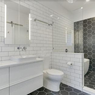 Exempel på ett mellanstort modernt vit vitt en-suite badrum, med släta luckor, vita skåp, ett fristående badkar, våtrum, en toalettstol med separat cisternkåpa, vit kakel, tunnelbanekakel, vita väggar, klinkergolv i porslin, ett undermonterad handfat, bänkskiva i kvarts, svart golv och dusch med gångjärnsdörr