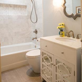 Modelo de cuarto de baño tradicional renovado, pequeño, con armarios tipo vitrina, puertas de armario blancas, bañera empotrada, ducha empotrada, sanitario de una pieza, baldosas y/o azulejos blancos, baldosas y/o azulejos de piedra, paredes grises, suelo de baldosas de porcelana, lavabo bajoencimera y encimera de cuarcita