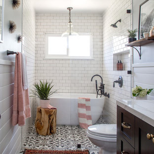 ロサンゼルスの中くらいのカントリー風おしゃれなバスルーム (浴槽なし) (シェーカースタイル扉のキャビネット、置き型浴槽、白いタイル、サブウェイタイル、アンダーカウンター洗面器、茶色いキャビネット、バリアフリー、分離型トイレ、グレーの壁、セメントタイルの床、大理石の洗面台、黒い床、オープンシャワー) の写真