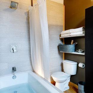 Diseño de cuarto de baño principal, rural, grande, con armarios con paneles lisos, puertas de armario de madera en tonos medios, bañera encastrada, combinación de ducha y bañera, sanitario de una pieza, baldosas y/o azulejos blancos, baldosas y/o azulejos de cerámica, paredes marrones, suelo de bambú, lavabo suspendido, encimera de cemento y suelo marrón