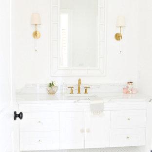 Modelo de cuarto de baño clásico renovado, grande, con puertas de armario blancas, armarios con paneles lisos, paredes blancas, suelo de linóleo, lavabo bajoencimera, encimera de mármol y encimeras blancas