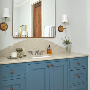 Inspiration for a small beach style master bathroom in Grand Rapids with recessed-panel cabinets, blue cabinets, grey walls, ceramic floors, an undermount sink, limestone benchtops, beige floor and beige benchtops.