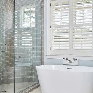 Idéer för små maritima beige en-suite badrum, med luckor med infälld panel, blå skåp, ett fristående badkar, en dusch i en alkov, grå kakel, keramikplattor, grå väggar, klinkergolv i keramik, ett undermonterad handfat, bänkskiva i kalksten, beiget golv och dusch med gångjärnsdörr