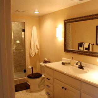 カンザスシティの中サイズのトラディショナルスタイルのおしゃれなバスルーム (浴槽なし) (アルコーブ型シャワー、ベージュの壁、大理石の床、一体型シンク、マルチカラーの床、開き戸のシャワー、レイズドパネル扉のキャビネット、白いキャビネット、分離型トイレ) の写真