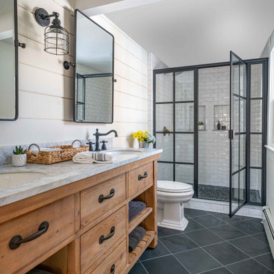 Mid-sized transitional master white tile and subway tile slate floor, gray floor, double-sink and shiplap wall bathroom photo in Boston with medium tone wood cabinets, white walls, an undermount sink, marble countertops, a hinged shower door, white countertops, a built-in vanity and a niche
