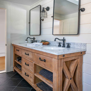 This is an example of a mid-sized country master bathroom in Boston with medium wood cabinets, white tile, subway tile, white walls, slate floors, an undermount sink, marble benchtops, grey floor, a hinged shower door, white benchtops, a double vanity, a built-in vanity and planked wall panelling.
