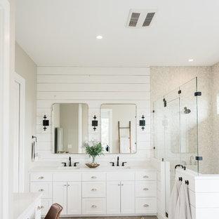 オースティンの大きいトランジショナルスタイルのおしゃれなマスターバスルーム (シェーカースタイル扉のキャビネット、白いキャビネット、置き型浴槽、ダブルシャワー、ベージュのタイル、石タイル、グレーの壁、磁器タイルの床、アンダーカウンター洗面器、珪岩の洗面台、グレーの床、開き戸のシャワー、白い洗面カウンター) の写真