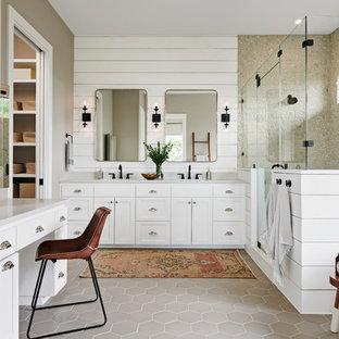 オースティンのトランジショナルスタイルのおしゃれなマスターバスルーム (シェーカースタイル扉のキャビネット、白いキャビネット、置き型浴槽、ベージュのタイル、グレーの壁、磁器タイルの床、アンダーカウンター洗面器、グレーの床、開き戸のシャワー、グレーの洗面カウンター、石タイル、コーナー設置型シャワー) の写真