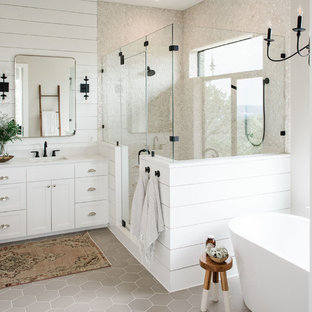 オースティンの広いカントリー風おしゃれなマスターバスルーム (シェーカースタイル扉のキャビネット、白いキャビネット、置き型浴槽、コーナー設置型シャワー、白い壁、磁器タイルの床、オーバーカウンターシンク、クオーツストーンの洗面台、グレーの床、開き戸のシャワー、白い洗面カウンター) の写真