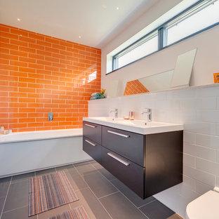 Diseño de cuarto de baño actual con armarios con paneles lisos, puertas de armario de madera en tonos medios, bañera empotrada, baldosas y/o azulejos naranja, paredes blancas y suelo gris