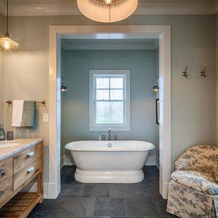 Ejemplo de cuarto de baño principal, campestre, de tamaño medio, con armarios con paneles lisos, puertas de armario de madera oscura, bañera exenta, baldosas y/o azulejos grises, baldosas y/o azulejos blancos, baldosas y/o azulejos de porcelana, paredes grises, suelo de pizarra, lavabo bajoencimera, encimera de mármol y suelo gris