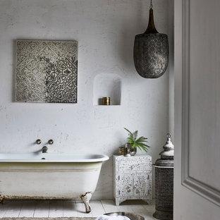 Imagen de cuarto de baño infantil, mediterráneo, grande, con armarios tipo mueble, puertas de armario blancas, bañera exenta, paredes blancas, suelo de madera pintada y suelo blanco