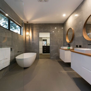 Inspiration for a contemporary master bathroom in Brisbane with flat-panel cabinets, white cabinets, a freestanding tub, a corner shower, gray tile, grey walls, a vessel sink, wood benchtops, grey floor, an open shower and brown benchtops.