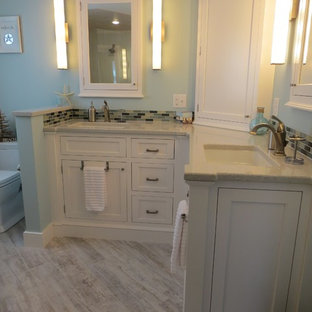 Walk-in shower - mid-sized beach style master multicolored tile and glass tile porcelain floor walk-in shower idea in Portland Maine with an undermount sink, beaded inset cabinets, white cabinets, quartz countertops, a two-piece toilet and blue walls