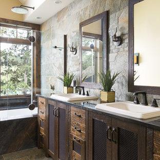 На фото: главная ванная комната среднего размера в стиле рустика с фасадами островного типа, коричневыми фасадами, полновстраиваемой ванной, душем над ванной, плиткой из сланца, полом из сланца, накладной раковиной, столешницей из гранита, разноцветной столешницей, серой плиткой, желтыми стенами, серым полом и открытым душем с
