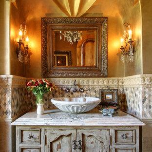 Foto di un'ampia stanza da bagno padronale mediterranea con ante lisce, ante in legno chiaro, vasca idromassaggio, doccia doppia, WC monopezzo, piastrelle beige, piastrelle in pietra, pareti beige, pavimento in travertino, lavabo integrato e top piastrellato