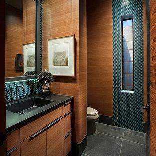 Modelo de cuarto de baño con ducha, de estilo americano, grande, con armarios con paneles lisos, puertas de armario de madera oscura, baldosas y/o azulejos azules, baldosas y/o azulejos en mosaico, suelo de pizarra, lavabo encastrado, encimera de ónix y suelo negro