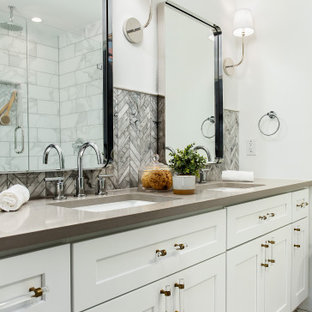 Ispirazione per una stanza da bagno padronale costiera di medie dimensioni con ante in stile shaker, ante bianche, piastrelle grigie, piastrelle a mosaico, pareti bianche, lavabo sottopiano, pavimento bianco e top grigio