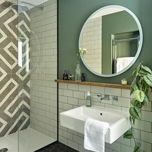 Diseño de cuarto de baño con ducha, minimalista, de tamaño medio, con armarios con paneles lisos, puertas de armario azules, ducha abierta, sanitario de pared, baldosas y/o azulejos grises, baldosas y/o azulejos de cemento, paredes verdes, suelo de baldosas de porcelana, lavabo suspendido, encimera de madera, suelo negro, ducha abierta y encimeras marrones