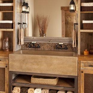 Foto på ett stort rustikt badrum, med ett avlångt handfat och kakel i småsten