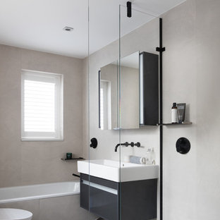 Photo of a medium sized contemporary bathroom in London with flat-panel cabinets, a built-in bath, grey walls, a wall-mounted sink, grey floors, an open shower, a wall mounted toilet, black cabinets, stone slabs and concrete flooring.
