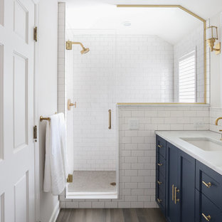 Elegant white tile and subway tile brown floor alcove shower photo in Minneapolis with shaker cabinets, blue cabinets, white walls, an undermount sink, a hinged shower door and white countertops