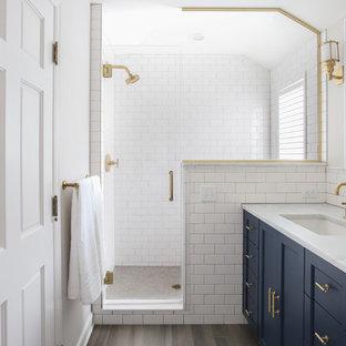 Modelo de cuarto de baño tradicional con armarios estilo shaker, puertas de armario azules, ducha empotrada, baldosas y/o azulejos blancos, baldosas y/o azulejos de cemento, paredes blancas, lavabo bajoencimera, suelo marrón, ducha con puerta con bisagras y encimeras blancas