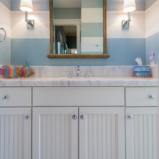 Inspiration for a mid-sized beach style kids' white tile and stone tile marble floor bathroom remodel in Miami with an undermount sink, recessed-panel cabinets, white cabinets, marble countertops, a one-piece toilet and blue walls