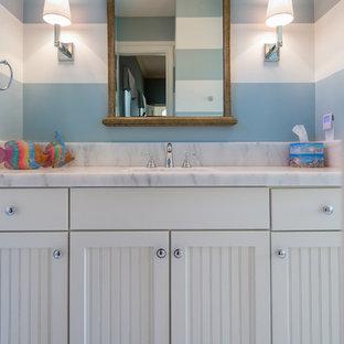 Inspiration för mellanstora maritima badrum för barn, med ett undermonterad handfat, luckor med infälld panel, vita skåp, marmorbänkskiva, ett badkar i en alkov, en öppen dusch, en toalettstol med hel cisternkåpa, vit kakel, stenkakel, blå väggar och marmorgolv