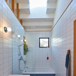Modelo de cuarto de baño contemporáneo con armarios con paneles lisos, puertas de armario de madera oscura, bañera encastrada sin remate, ducha a ras de suelo, baldosas y/o azulejos blancos, baldosas y/o azulejos de cemento, paredes blancas, lavabo tipo consola, suelo azul y ducha abierta