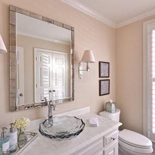 Kleines Klassisches Duschbad mit Aufsatzwaschbecken, profilierten Schrankfronten, weißen Schränken, Marmor-Waschbecken/Waschtisch, Toilette mit Aufsatzspülkasten, beiger Wandfarbe und dunklem Holzboden in Dallas