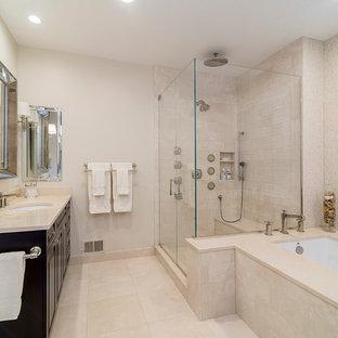 Immagine di una grande stanza da bagno padronale tradizionale con lavabo sottopiano, ante con bugna sagomata, ante in legno bruno, top in marmo, vasca sottopiano, doccia ad angolo, piastrelle beige, lastra di pietra, pareti beige e pavimento in marmo