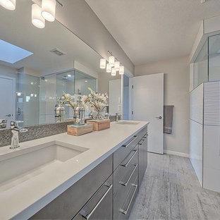 Cette image montre une grand salle de bain principale design avec un mur gris, un sol en contreplaqué, une baignoire posée, une douche d'angle, un lavabo encastré, un plan de toilette en quartz modifié, un placard à porte plane, des portes de placard grises, un sol gris et une cabine de douche à porte battante.