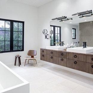 Пример оригинального дизайна: большая главная ванная комната в стиле современная классика с плоскими фасадами, темными деревянными фасадами, японской ванной, серой плиткой, керамической плиткой, белыми стенами, полом из цементной плитки, настольной раковиной, столешницей из дерева, белым полом и коричневой столешницей