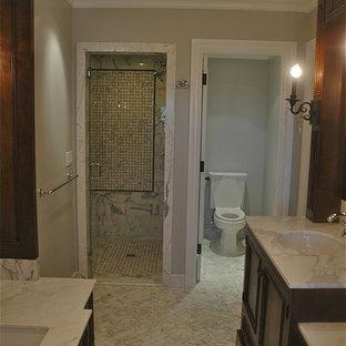 Exemple d'un sauna chic de taille moyenne avec un lavabo encastré, une baignoire encastrée, un WC séparé, des portes de placard en bois sombre, un plan de toilette en marbre, un carrelage blanc, un carrelage de pierre, un placard avec porte à panneau encastré et un sol en carrelage de céramique.